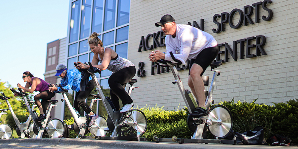 Adults taking a spin class outside fitness center facility
