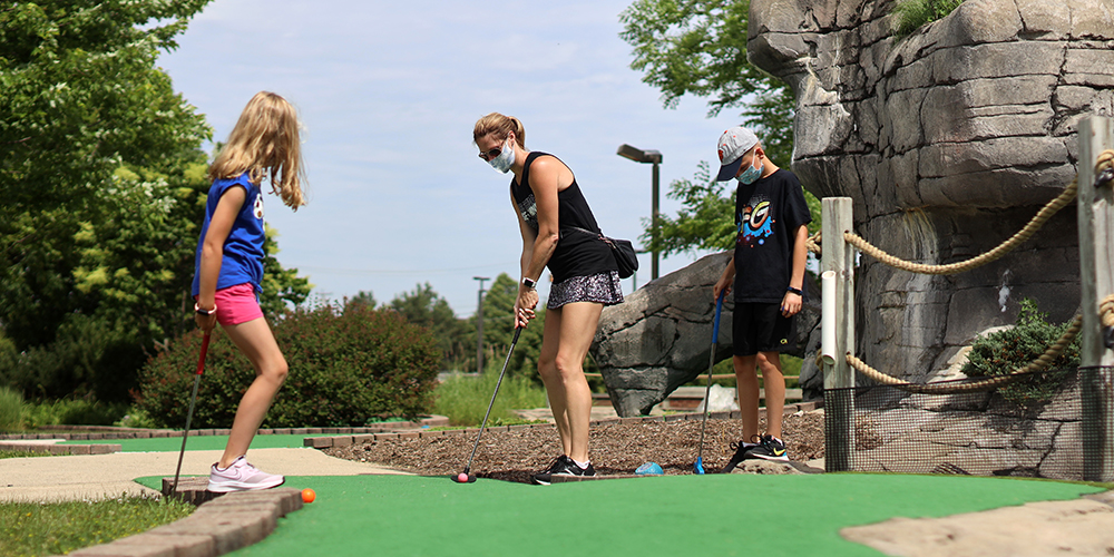 Family playing mini golf at Holes & Knolls