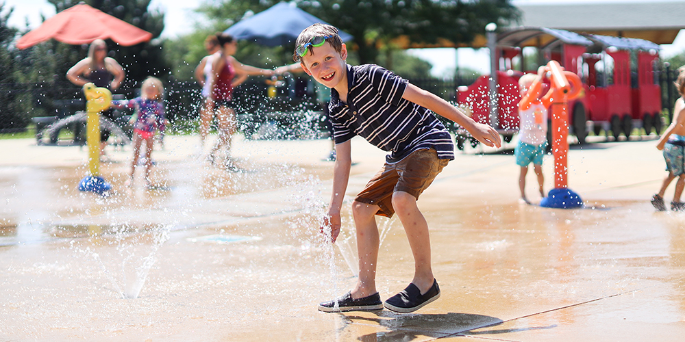 Boy smiling while playing in water at Maryknoll Splash Park