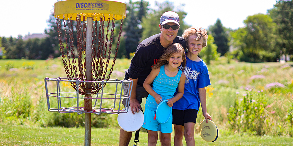 Family standing next to disc golf goal at Maryknoll Park