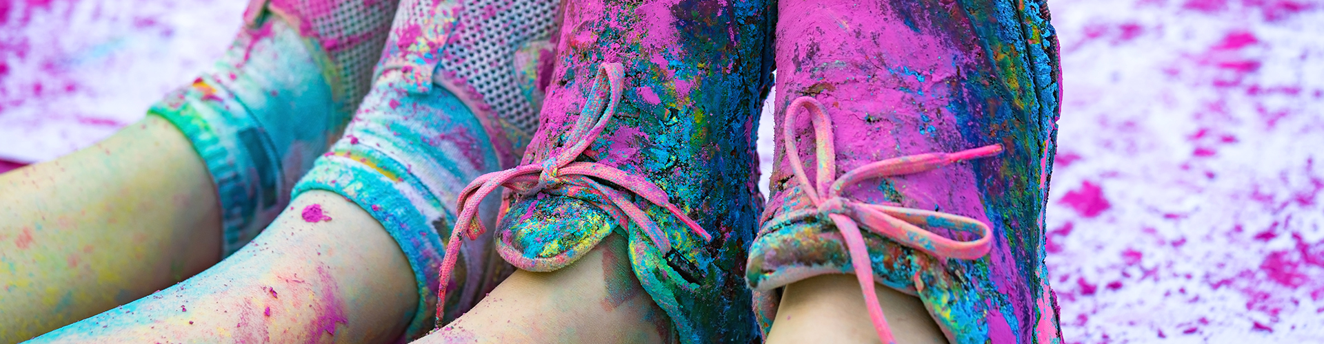 The colorful shoes and legs of teenagers with purple color powder in the public event The Color Run